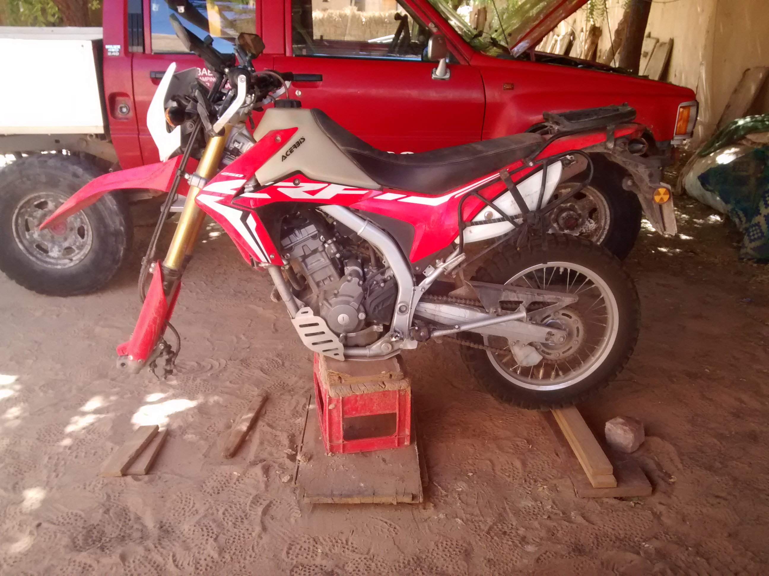 Honda CRF250L on makeshift stand with front wheel removed.
