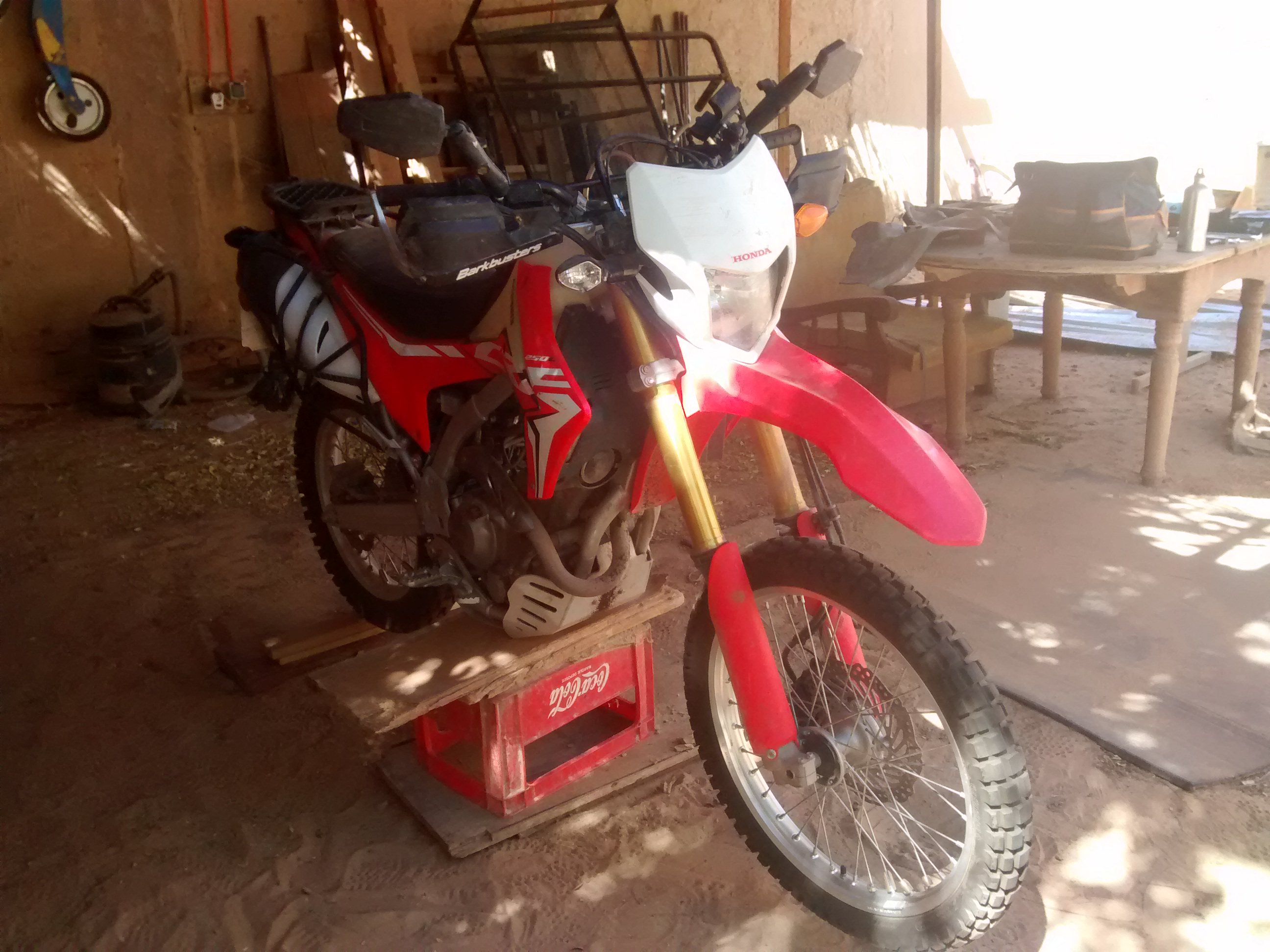 Honda CRF250L on makeshift stand to repair front rim.