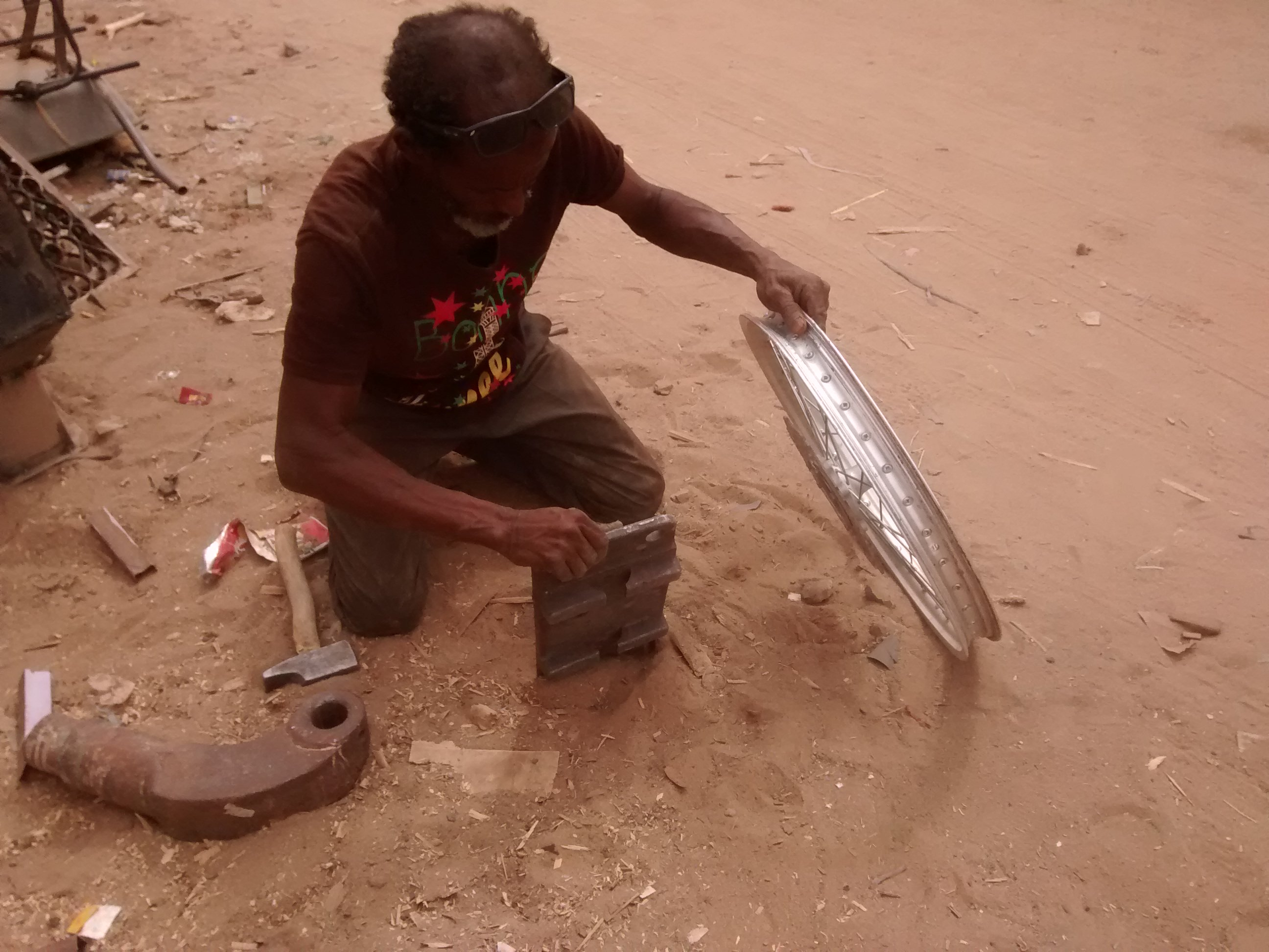 Blacksmith in Atar, Mauritania, working out dent and flat spot on front rim.