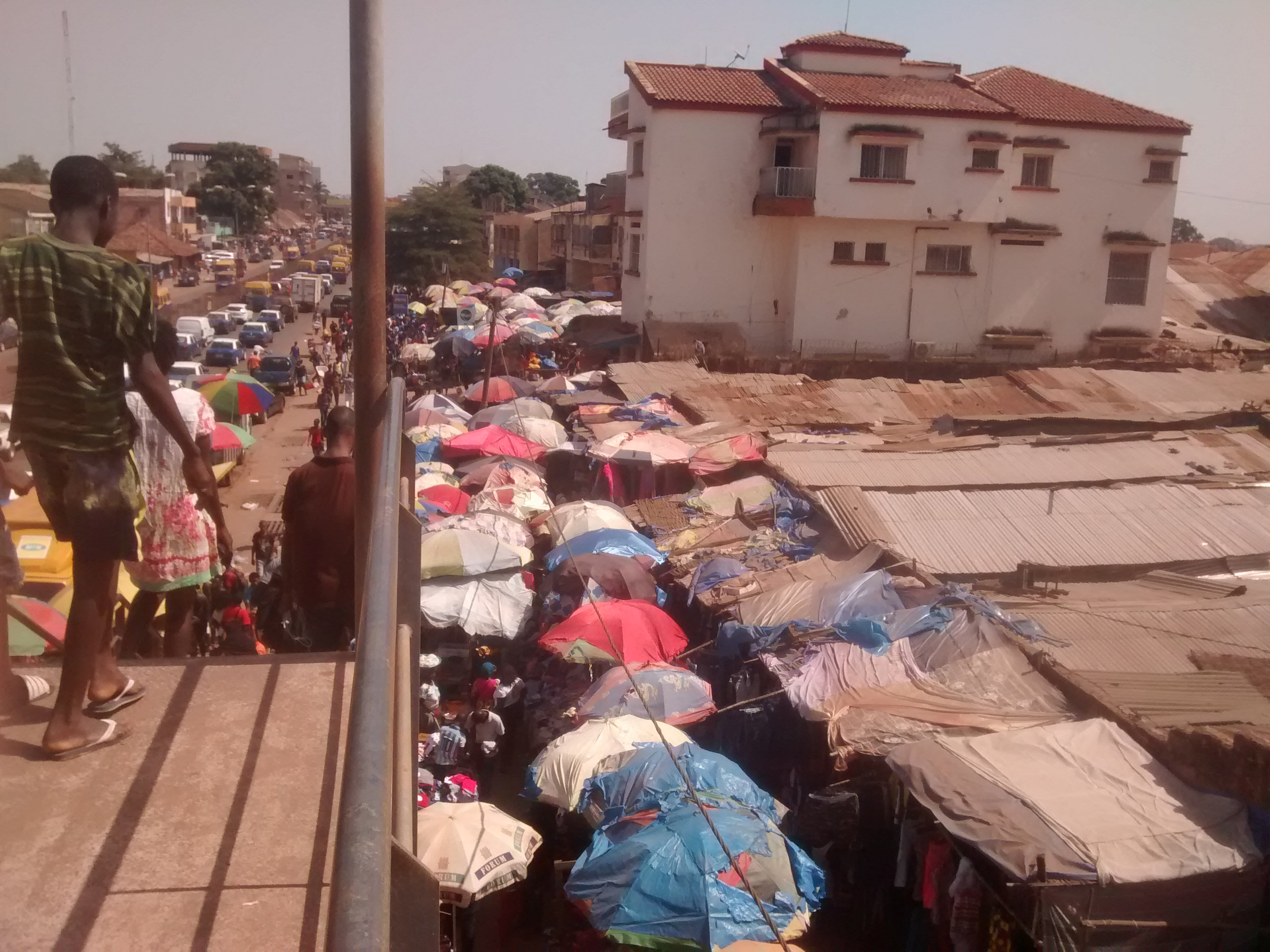 Market sprawling away from main road under corrugated roofing in Bissau, Guinea-Bissau.