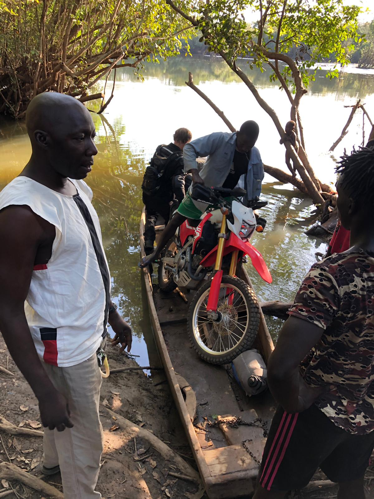 My motorcycle being loaded onto a paddle boat at River Kogon when leaving Guinea-Bissau from Contabane to enter Guinea.