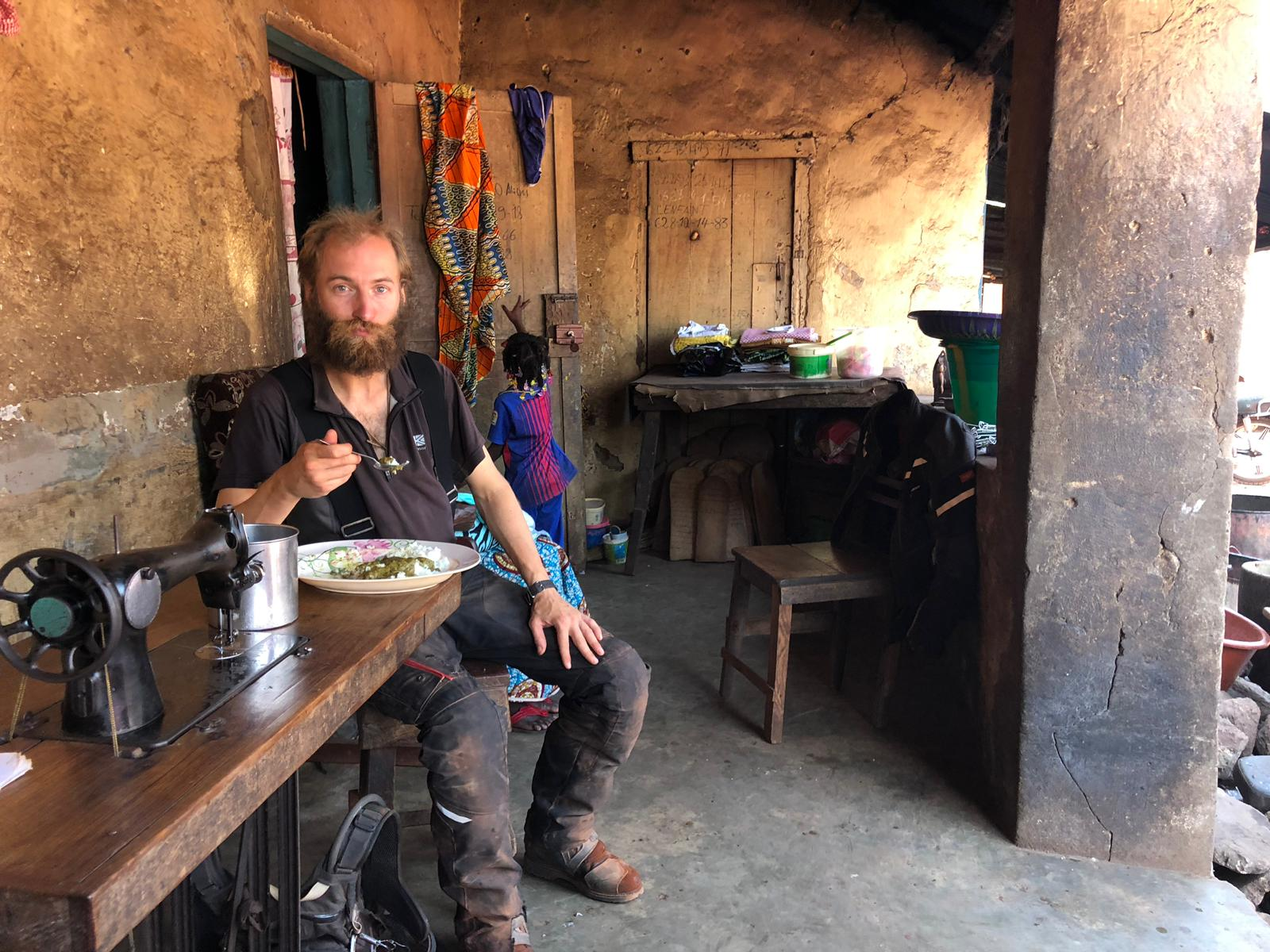 Eating rice and spinach in Boke, Guinea.
